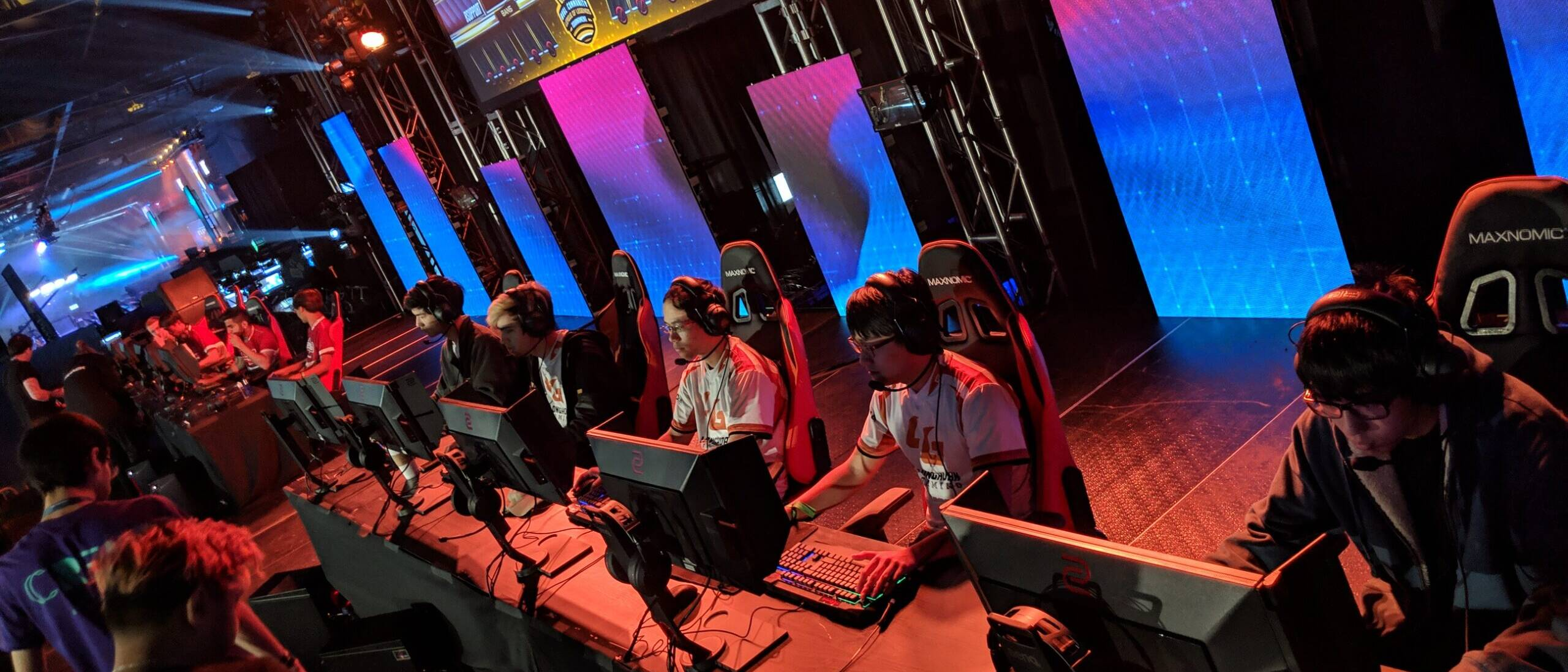 Longhorn Gaming team playing video games on computers on stage