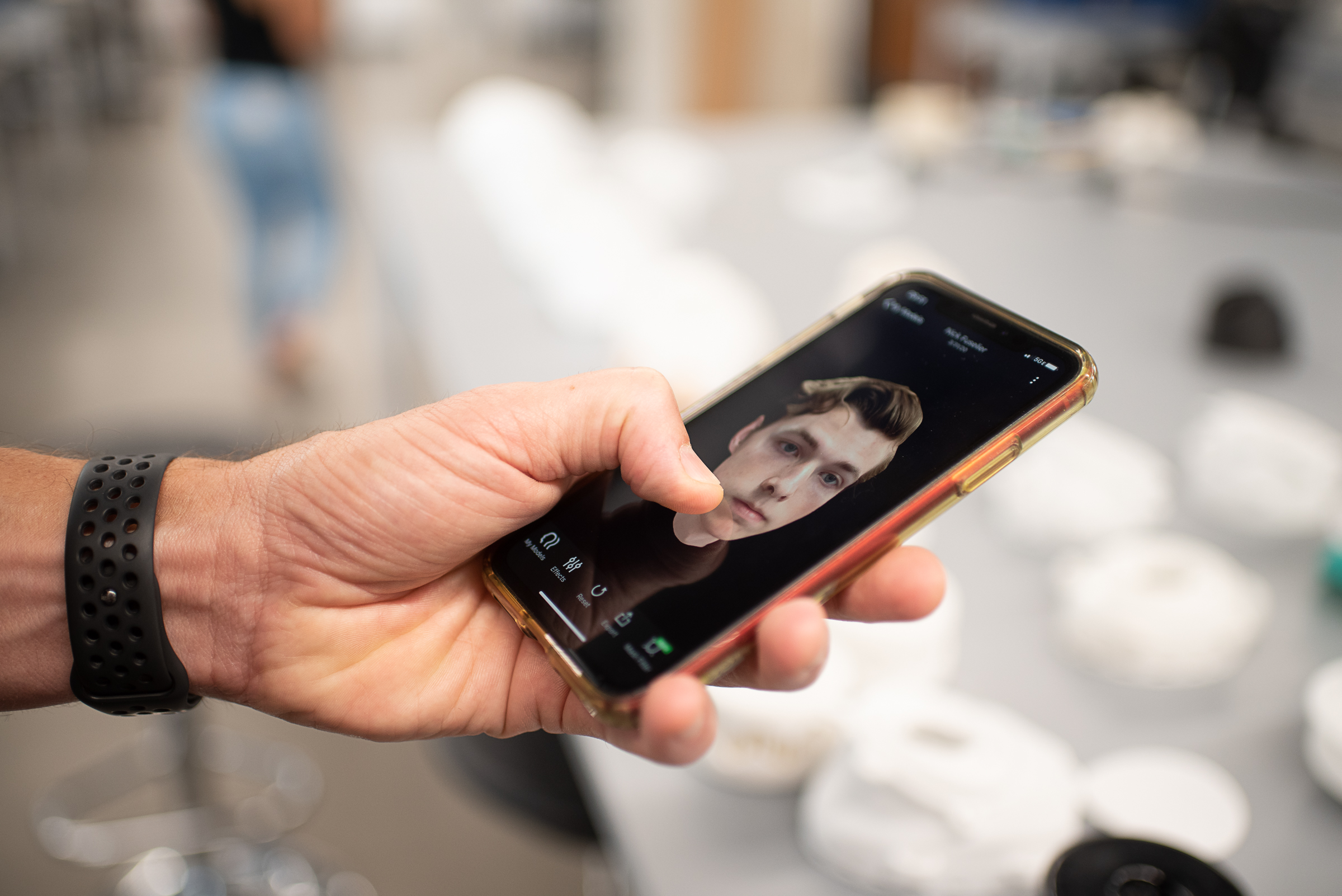 Scott Evans holds smart phone with 3D rendering of male face