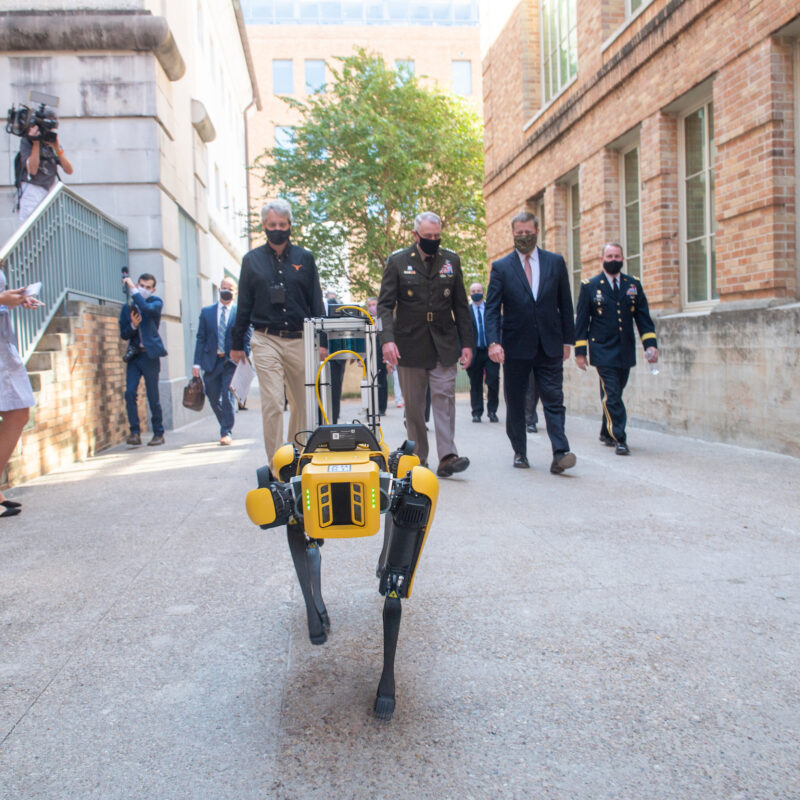 Boston Dynamics Robot walks down the sidewalk with group of people including Army men and researchers behind